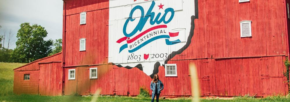 Posing with an Ohio Bicentennial mural on the side of a red barn